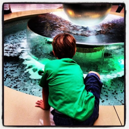 boy sitting on the edge of a mall fountain