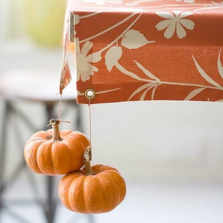 DIY fall decoration with little pumpkins as tablecloth weights