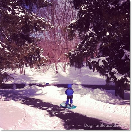 boy sledding down a driveway, standing on sled