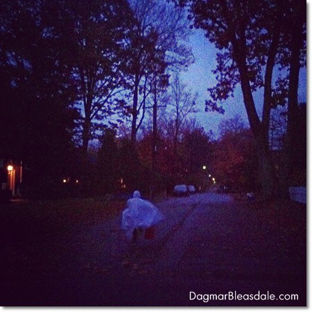 Boy dressed as ghost on Halloween running down street