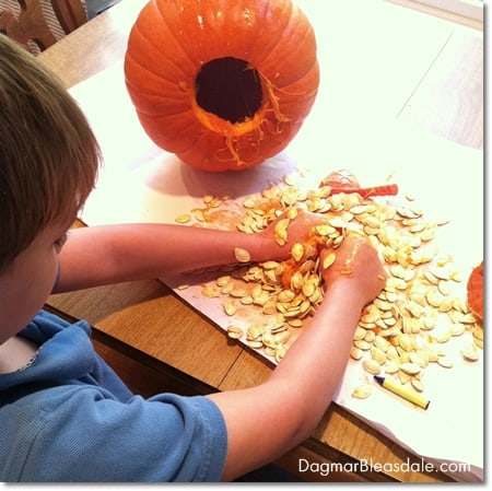 boy getting messy taking out the inside of pumpkin