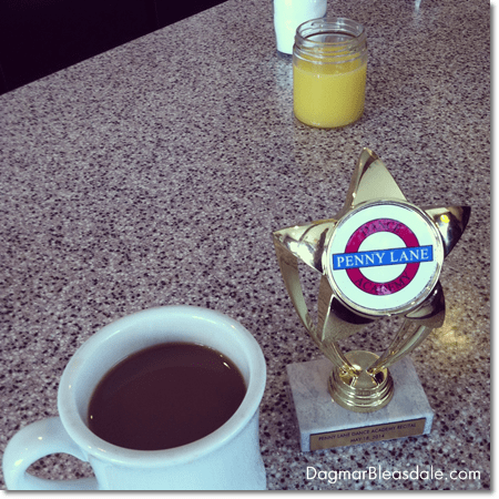 coffee cup and dance recital trophy on diner counter